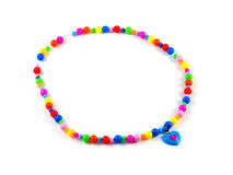 Plastic multi-colored beads isolated. Plastic children's multi-colored beads with blue heart isolated on white Royalty Free Stock Image