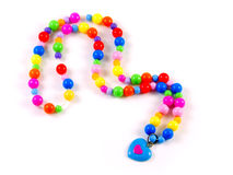 Plastic multi-colored beads isolated on white. Plastic children's multi-colored beads with blue heart isolated on white Stock Photography