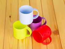 Plastic multi-colored cups on a background  light wood. Stock Photography