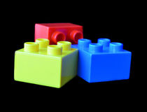 Plastic multicoloured blocks of the constructor on the black background Stock Photography