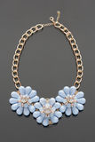 Plastic necklace. three blue flower Royalty Free Stock Photos