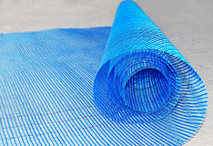 Plastic net roll. Blue plastic net roll rolled out over concrete Stock Images