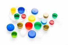 Plastic noten en kappen op een wit concept als achtergrond/recyclings stock afbeelding