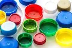Plastic noten en kappen op een wit concept als achtergrond/recyclings stock afbeeldingen