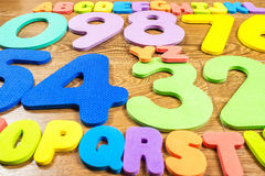 Plastic numbers and letters on wooden background Stock Photography