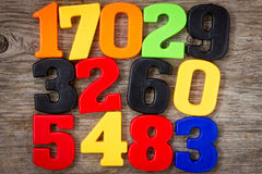 Plastic numbers on the wooden background stock photos