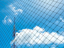 Plastic nylon net front of signal tower. Under the blue sky and cloud background Royalty Free Stock Photo
