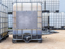 Plastic olie of vloeibare containers met metaalkooi stock afbeeldingen