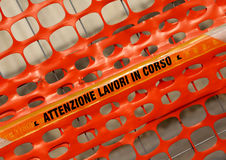 Plastic orange safety net with words ATTENZIONE LAVORI IN CORSO Stock Photo