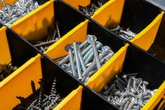 Organizer for storage of a large number of screws. It is yellow - black color. Horizontal photo. Close up stock photography