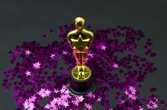 Plastic Oscar award with pink stars confetti royalty free stock photo