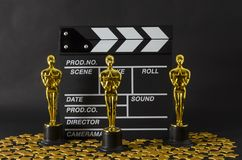 Plastic Oscar awards, a clapboard and golden stars confetti. XALAPA, VERACRUZ, MEXICO- FEBRUARY 14, 2019: Plastic Oscar awards, a clapboard and golden stars stock photography