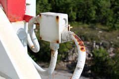 Free Plastic Outdoor Electrical Connection Box With Three Damaged Wires Connected From All Sides Mounted On Metal Pipe With Dense Royalty Free Stock Image - 141017856