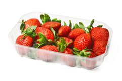 Plastic packaging of fresh juicy strawberries. Saturated colors. White isolated background. royalty free stock image