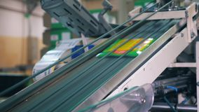 Plastic packaging moving up on automated conveyor at a factory.