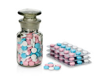 Plastic packing and glass vial with pills of different colour. Royalty Free Stock Photos