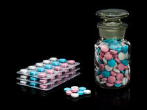 Plastic packing and glass vial with pills of different colour. Royalty Free Stock Photography