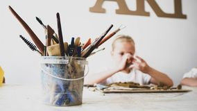 Tools for sculpting in art workshop with blurred child girl on background. Plastic pail with tools for painting, brushes and pencils is on the table and child royalty free stock images