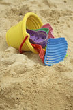 Plastic pail and toys on beach. Yellow child's plastic bucket with colorful shovels and sand toys lying on side on sand Stock Images