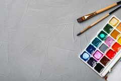 Plastic palette with colorful paints and brushes. On grey background, top view Royalty Free Stock Photos