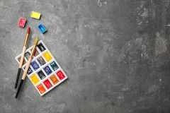 Plastic palette with colorful paints and brushes. On table, top view Royalty Free Stock Photo