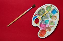 Plastic palette with gouache paint and brush on a red paper background. Top view.  royalty free stock image