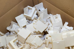 Plastic parts are packed in a cardboard box Royalty Free Stock Photography