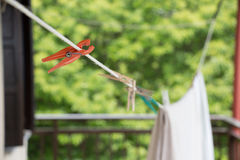 A plastic peg on a washing line. Closeup of a plastic peg on a washing line with clothespins and clothes blurred background Royalty Free Stock Photos