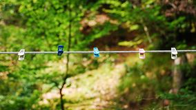 Plastic Pegs on Line. Five plastic clothes pegs on a rope washing line in a forested area of Slovenia Stock Images