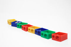 Plastic pencil sharpeners. A row of primary colored plastic pencil sharpeners Royalty Free Stock Photography