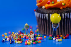 Plastic People Cleaning Up a Messy Cupcake. Miniature Plastic People Cleaning Up a Messy Cupcake Royalty Free Stock Photos