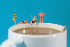 Plastic People Swimming in Coffee. Miniature Plastic People Swimming in Coffee Stock Photos