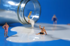 Plastic People Swimming in Milk. Miniature Plastic People Swimming in Milk Stock Photo