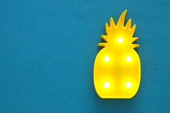 A plastic pineapple lamp with leds over blue wooden background. holiday summer concept. A plastic pineapple lamp with leds over blue wooden background. holiday royalty free stock photography