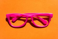 Plastic pink eyeglasses isolated on orange background. Funny hipsters concept stock photography