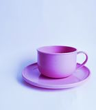 Plastic pink teacup and saucer. Pink plastic teacup and saucer on a white background Stock Photography