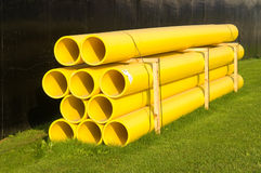 Plastic pipes. Yellow plastic construction pipes stacked on green grass Royalty Free Stock Photos