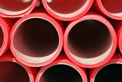 Plastic pipes. Red plastic pipes stacked. Industrial concept Royalty Free Stock Images