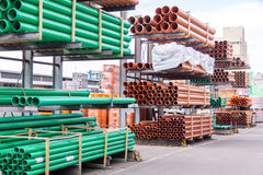 Plastic pipes in a factory or warehouse yard. Plastic pipes stacked in a factory or warehouse yard for use in plumbing or sewage installations on a construction Royalty Free Stock Photography