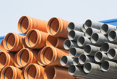 Plastic pipes. Orange and gray , in different sizes, stacked together at a warehouse Stock Photos