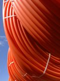 Plastic pipes stacked in rolls on the street. On the sky background royalty free stock image