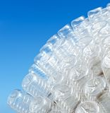 Plastic Planet. Lots of transparent plastic bottles shown in the background of blue sky Royalty Free Stock Photo