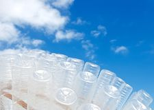 Plastic Planet. Lots of transparent plastic bottles shown in the background of blue sky Stock Photo