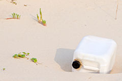 Plastic pollution. Plastic container on a beach Royalty Free Stock Photos