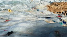 Plastic pollution on beach. Waves hitting ashore on a beach with lot of plastic trash stock footage