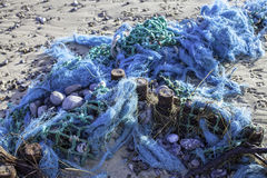 Plastic pollution - blue tangled fishing nets washed up on the b Stock Image
