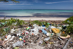 Plastic Pollution on Caribbean Beach. Plastic trash has washed up on a remote beach in the Caribbean Sea. Plastic breaks down into tiny pieces that eventually royalty free stock photos