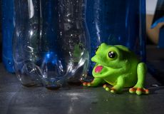 A toy frog sitting behind plastic bottles. The topic of this is image is plastic environment pollution royalty free stock image