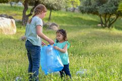 Kids cleaning in park.Volunteer children with a garbage bag cleaning up litter, putting plastic bottle in recycling bag. stock image