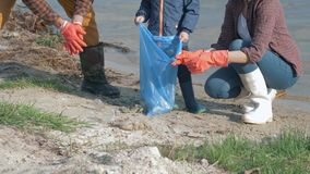 Plastic pollution, man and woman with kid boy in rubber gloves collects trash in garbage bag while cleaning dirty beach. Close up stock footage